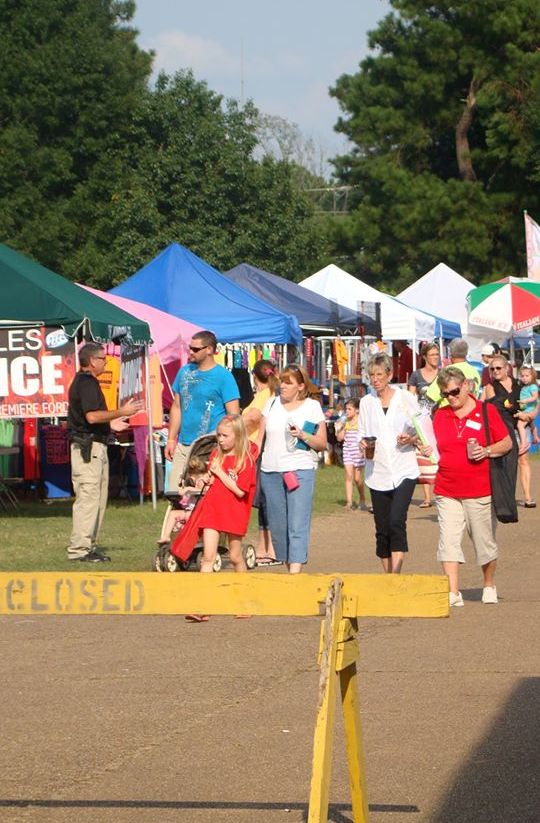 Festival goers walk along smokers and vendors at Roast-N-Boast 2013 in Columbus, MS